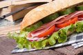 Ciabatta with ham and vegetables on a background of books closeup an old wooden table horizontal Royalty Free Stock Photography