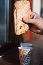 Ciabatta in hand with a cardboard cup of coffee Royalty Free Stock Photo