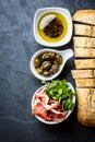 Ciabatta, pepper oil, jamon ham serrano, arugula, rosemary, slate background Royalty Free Stock Photo
