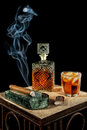 Cigar and glass of brandy a smoking sits beside a crystal decanter alcohol Royalty Free Stock Photography
