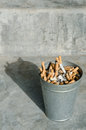 Cigarette in aluminium bin with concrete background Stock Photo