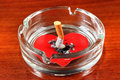 Cigarette in ashtray with heart shape on the table Stock Photos