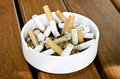 Cigarette in bin ceramic on wood table background Royalty Free Stock Photo