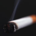 Cigarette on a black background as symbol of human dependence addictions Stock Image