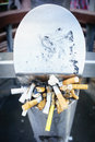 Cigarette butts stuffed into an on street receptacle packed tight and dirty Stock Photos