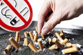 Cigarette stubs in ash and no smoking sign. Royalty Free Stock Photo