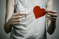 Cigarettes, addiction and public health topic: smoker holds the cigarette in his hand and a red heart on a dark background in the Royalty Free Stock Photo