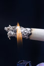 Cigarettes and flame the flames lit a cigarette leaving a green smoke Royalty Free Stock Photo
