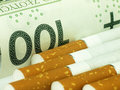 Cigarettes and money expensive habit smoking is on background Stock Photo