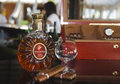 Cigars and bottle of remi martin cognac still life with cigar box glass in the bar with blur barman on the background Royalty Free Stock Photography