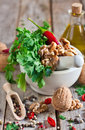 Cilantro and walnuts in a mortar red hot pepper white ceramic on wooden table Stock Photo