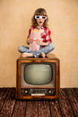 Cinema child playing at home kid sitting on retro tv and eating popcorn concept Royalty Free Stock Image