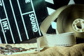 Cinema clapper and video film negative movie on a rough cloth. Royalty Free Stock Photo