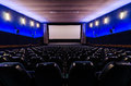 Cinema hall dark blue auditorium in the white screen in foreground Stock Images