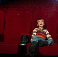 In a cinema smiling little boy watching movie Stock Photos