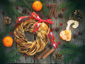 Cinnamon cocoa brown sugar wreath buns. Sweet Homemade christmas baking. Roll bread, tangerines, decoration on wooden background. Royalty Free Stock Photo