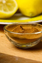 Cinnamon powder in front of lemon cut on yellow plate Royalty Free Stock Photography
