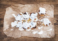 Cinnamon rolls with cream cheese icing on piece of oily craft paper over rustic wooden background Royalty Free Stock Photo