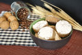 Cinnamon shortbread in a brown bowl and some ingredients like coffee wheat and nuts on a wooden table on a black and white Stock Image