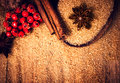 Cinnamon sticks brown sugar and anise star with red berries on wooden table close up still life festive food background Royalty Free Stock Images