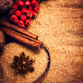 Cinnamon sticks brown sugar and anise star and on wooden table with red berries close up still life festive food background Stock Images