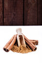 Cinnamon sticks and cinnamon powder on wood floor Stock Photos