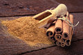 Cinnamon sticks and cinnamon powder on wood floor Royalty Free Stock Images