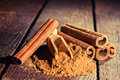 Cinnamon sticks and cinnamon powder on wood floor Royalty Free Stock Photography