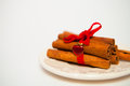 Cinnamon Sticks connected by a red tape on a white background fo Royalty Free Stock Photo