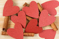 Cinnamon sticks and red hearts on a wooden background Royalty Free Stock Photo