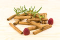 Cinnamon sticks on a wodden plate with raspberrys Royalty Free Stock Image