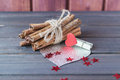 Cinnamon stocks with silver heart decorated with cloth pin and red sparkling stars on wooden planks St.Valentine's Day Royalty Free Stock Photo