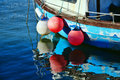 A circle of buoys small fishing boat with colourful floats and reflections Stock Image