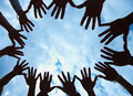 Circle of hands held out in unity against blue sky Royalty Free Stock Image