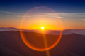 Circle sun reflexion at sunset over mountains the Stock Photography