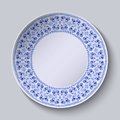 Circular blue flower pattern with empty space in the center. White porcelain plate with a stylized pattern in ethnic style.
