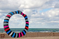 Circular colorful kite on the beach with fence Stock Photos