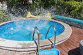 Circular outdoor pool. Water sprays from the pool. The young man jumped into the pool and the water sprang out.