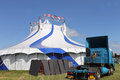 Circus tent and blue sky white with articulated lorry in foreground Stock Photo