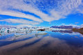 Cirrus clouds are reflected in the ocean lagoon beautifully smooth water of jökulsárlón glacial iceland Royalty Free Stock Images