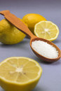 Citric acid in wooden spoon on blue background and lemons Stock Images