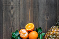 Citrus concept. Oranges, pineapple and mandarins on wooden table background top view copyspace