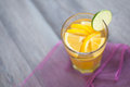 Citrus flavour tea hot served with orange and lemon slices full of spices winter time drink on violet tablecloth Stock Photo