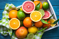 Citrus fruit in wooden tray on blue table. Royalty Free Stock Photo