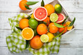 Citrus fruit in wooden tray on white table. Royalty Free Stock Photo