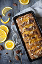 Citrus plumcake with pecan walnuts on mold on table with fresh orange Royalty Free Stock Photo
