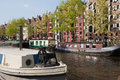 City of amsterdam in netherlands barges and houseboats on a canal and historic apartment buildings former warehouses holland Royalty Free Stock Photo