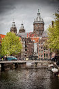 City of amsterdam in netherlands bridge canal historic buildings and towers saint nicholas church the background Royalty Free Stock Photos