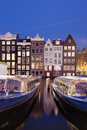 City of amsterdam at night historic canal houses with passenger tour boats on the first plan netherlands north holland Royalty Free Stock Photo