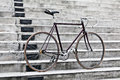 City bicycle and concrete stairs vintage style fixed gear retro road bike over gray urban background Stock Photo